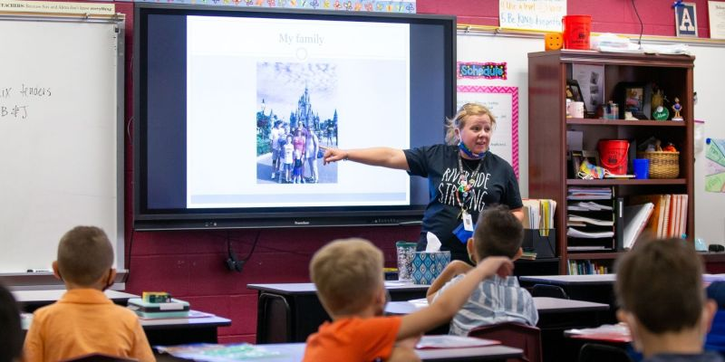 Riverside Teacher pointing to family picture at Disney displayed on projector in the front of her class