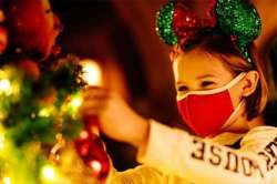 Young girl wearing holiday ears and a face covering touches tree.