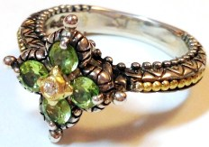 Peridot signature flower ring with diamond center and gold beading on shank. Size 8.