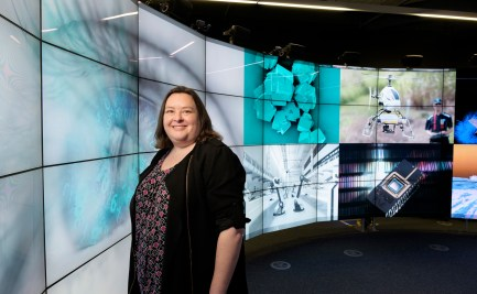 Danielle Kennedy standing in a darkened room looking at a wrap-around series of screens, each depicting an advanced manufacturing scene, such as drones and x-ray analysis.