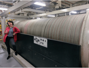 large spool of thick cable with woman leaning on spool