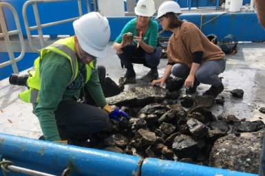two female and one one male in hardhats nad high vis vests look through a pile of rocks on ship deck