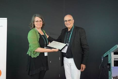Melissa James receives the best paper award from Professor Mattheos Santamouris at the International High-Performance Built Environments Conference.