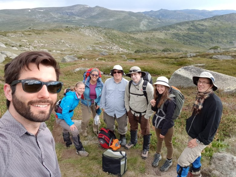 Seven people standing together with Kosciusko National Park mountains as the background.