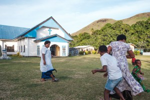 Kids and parents playing outside on the grass in front of a church in Fiji
