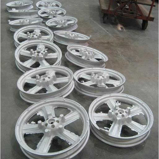 two rows of 6 of wheel castings for motorbikes. They are each circular with spiral design for the support of motorcycles
