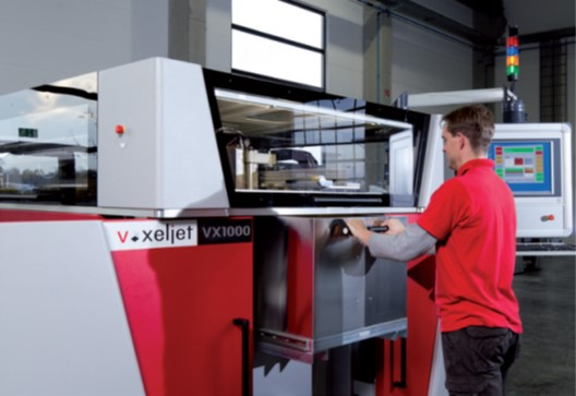 Man using the Voxelject VX1000. Its a large box like device with clear screen to see printing as it occurs