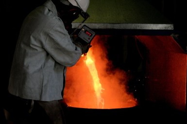 Worker measuring temperature of molten metal in smelting furnance