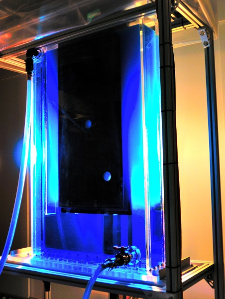 Large sheet of metal in a glass tank filled with blue coloured solution