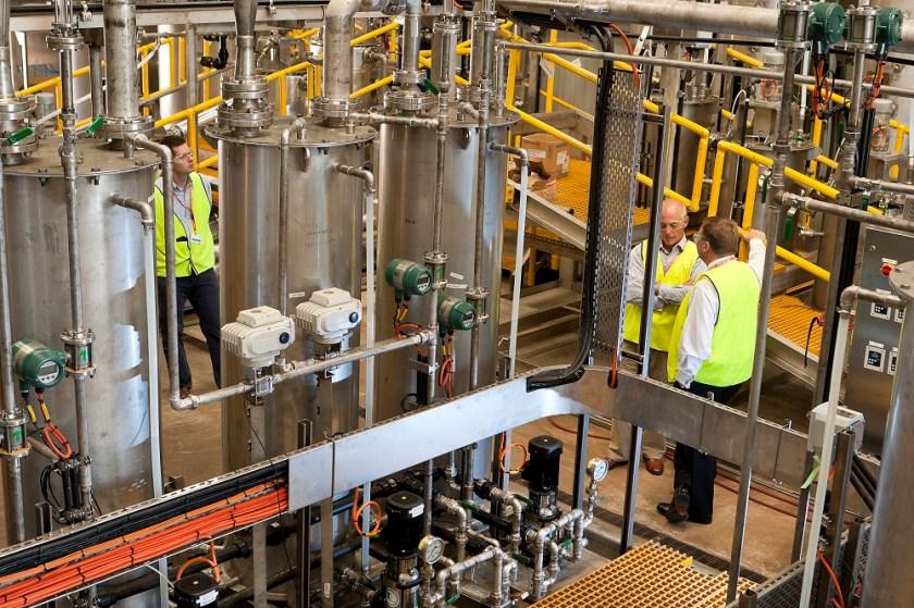 Three people in hi-vis working in industrial processing plant