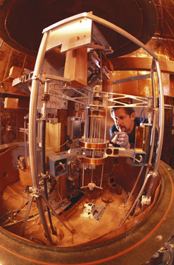 Physicist Richard Steiner adjusts the electronic kilogram, an experimental apparatus for defining mass in terms of the basic properties of nature. (NIST)