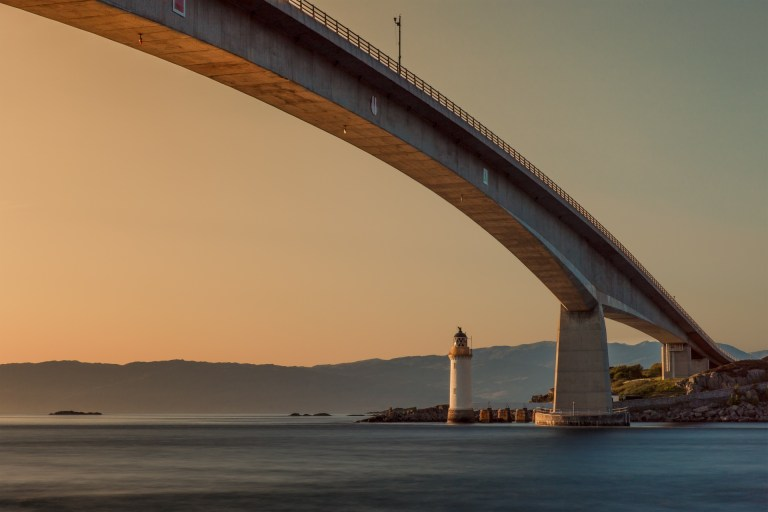 Bridge across water with mountain range in background, next to lighthouse, sunset orange sky