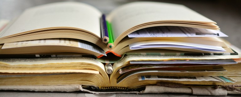 Pile of open books with paper and notes in the leaves and pens and pencils in the books