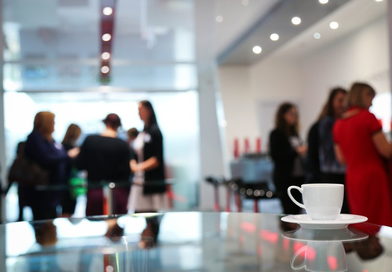 Image of coffee cup in foreground and blurry people standing around in groups in the background.