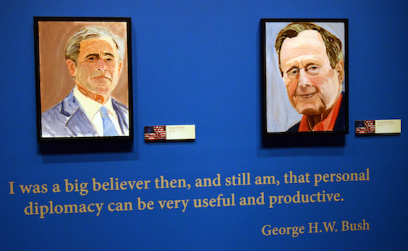 "Portraits of former Presidents Goerge W. Bush, left, and his father George H.W. Bush which are part of the exhibit ""The Art of Leadership: A President's  Diplomacy,"" are on display at the George W. Bush Presidential Library and Museum in Dallas, Friday, April 4, 2014. The exhibit of world leader portraits painted by George W. Bush opens Saturday and runs through June 3.  (AP Photo/Benny Snyder)"