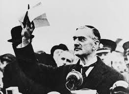 Le premier ministre britannique Neville Chamberlain tenant une copie de la déclaration supplémentaire britannique-allemande [1] à sa descente d'avion après le retour de Munich, septembre 1938.