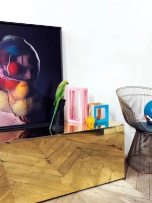 Sur un bahut en miroir dessiné par Jean-Christophe Aumas, un perroquet naturalisé de chez Design et Nature ; à droite, fauteuil en acier des années 60 (Knoll).