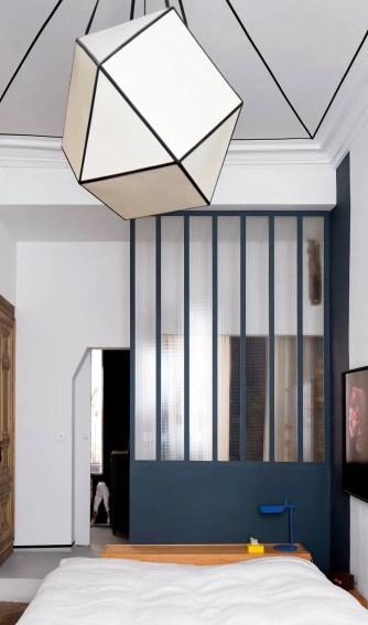 Dans la chambre, le plafond graphique est coordonné à la lampe dessinée par Thomas Boog. La cloison vitrée en acier a été achetée sur un marché aux puces à Paris.