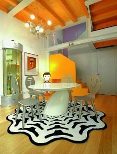 Le coin repas est représenté par une table « Parabel » d'Eero Aarnio entourée de chaises dorées d'Anna Gili pour Segni & Disegni, comme la lampe singe « Tambu ». Tapis créé en 2007 par Anna pour Memphis. Plafonnier avec carafes en verre Flos.