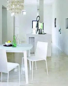 Espace petit-déjeuner. Sur le sol en ciment poli, la table « Gelso » en alu et verre blanc d'Antonio Citterio est entourée de chaises « Alma » (Roberto Barbieri), le tout B&B Italia. Entouré de cactées, un palmier sous la brise.