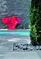 Face à la maison, les rougeoyantes courbes du fauteuil « Big E » de Ron Arad pour Moroso, accentuent l'ultra minéralité du bassin (Piscine Concept).