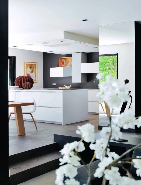 Avec l'îlot et le plan de travail, la décoratrice ajoute une note architecturée à la double ligne neutre formée par les éléments bas de la cuisine en Corian blanc, par une combinaison d'éléments Porro.