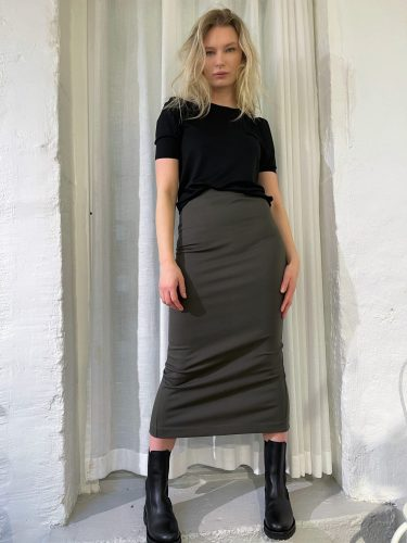 Girl wearing black Tu puff sleeve top and Lala Ecovero skirt green styled with boots