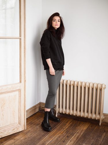 Girl wearing ricon black sweatshirt with Lala ecovero skirt in above ankle length styled with boots