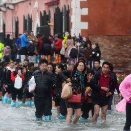 Tourists walk in the flooded Riva degli Schiavoni during a high-water (Acqua Alta) alert in Venice on October 29, 2018. - The flooding, caused by a convergence of high tides and a strong Sirocco wind, reached around 150 centimetres on October 29, 2018 (Photo by Miguel MEDINA / AFP)MIGUEL MEDINA/AFP/Getty Images