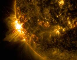 A solar flare bursts off the left limb of the sun in this image