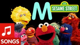 characters from Sesame Street show stand together with letter M and Sesame Street sign