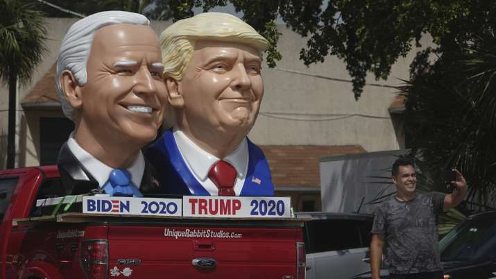 India Tv - A passerby stops to take a selfie with foam sculpture depictions of Donald Trump and Joe Biden.
