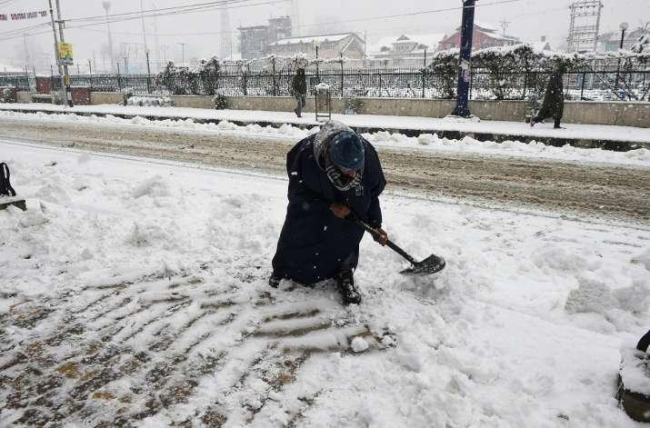 India Tv - Srinagar: A worker shovels snow from a footpath after a fresh snowfall in Srinagar, Sunday, Jan. 3, 2021.