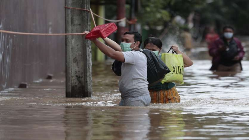 A man holds onto a safety line installed at a flooded neighborhood following heavy rains in Jakarta, Indonesia.
