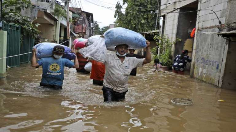 Indonesian men carry their belongings as they wade through the water at a flooded neighborhood following heavy rains in Jakarta, Indonesia.