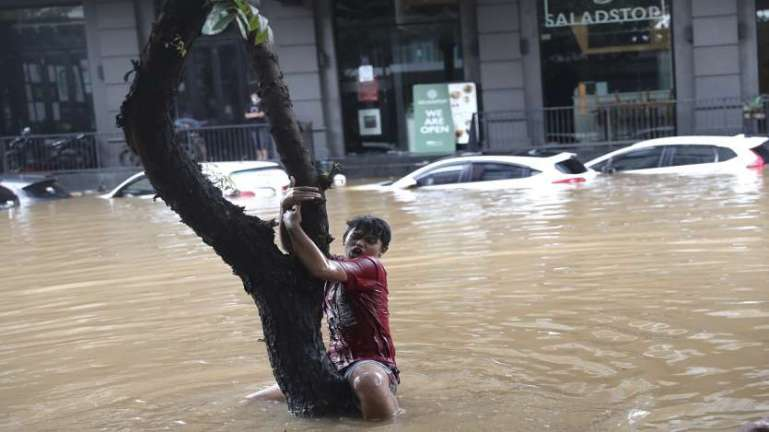 A man grabs a tree to keep from being swept away by flood water through a flooded neighborhood following heavy rains in Jakarta, Indonesia.