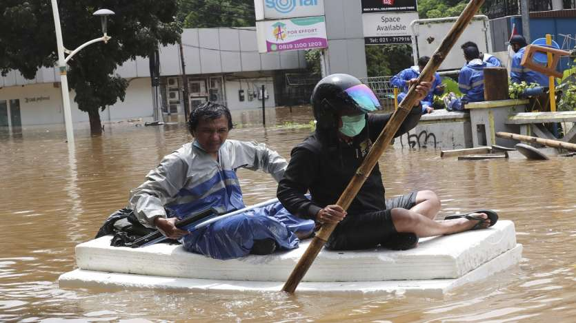Residents use a cork material as a raft to make their way through a flooded street following heavy rains in Jakarta, Indonesia.