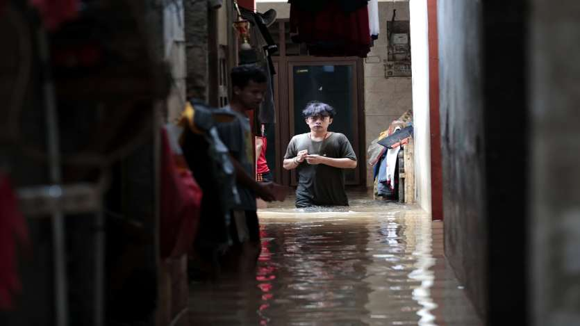 A man wades through the water at a flooded neighborhood following heavy rains in Jakarta, Indonesia.