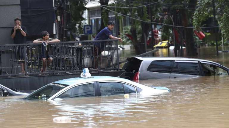 People stand above at an office yard flooded following heavy rains in Jakarta, Indonesia.