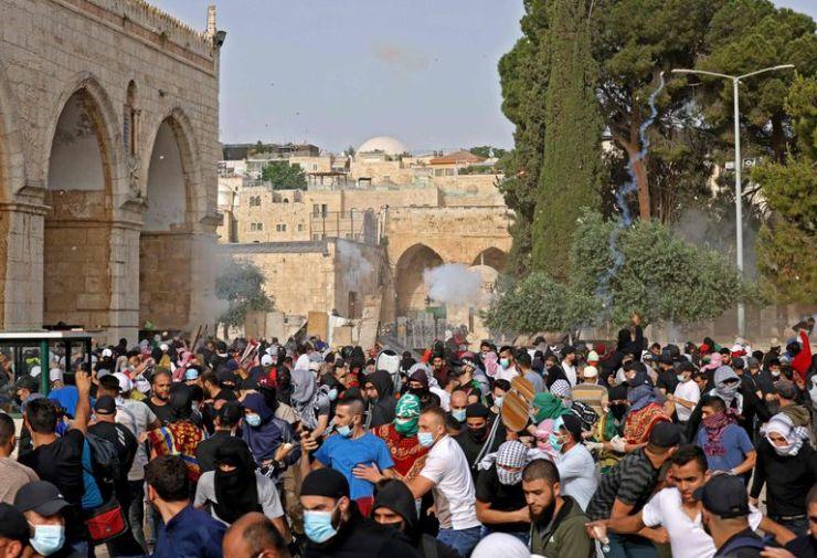 Palestinos correr por protección ante el lanzamiento de gases lacrimógenos por parte de la policía