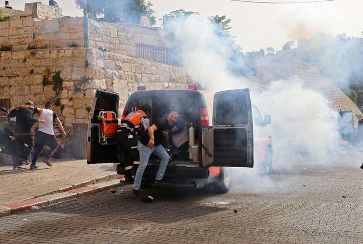 Los médicos palestinos evacuan a los manifestantes heridos mientras las fuerzas de seguridad israelíes disparan gases lacrimógenos en la Ciudad Vieja de Jerusalén