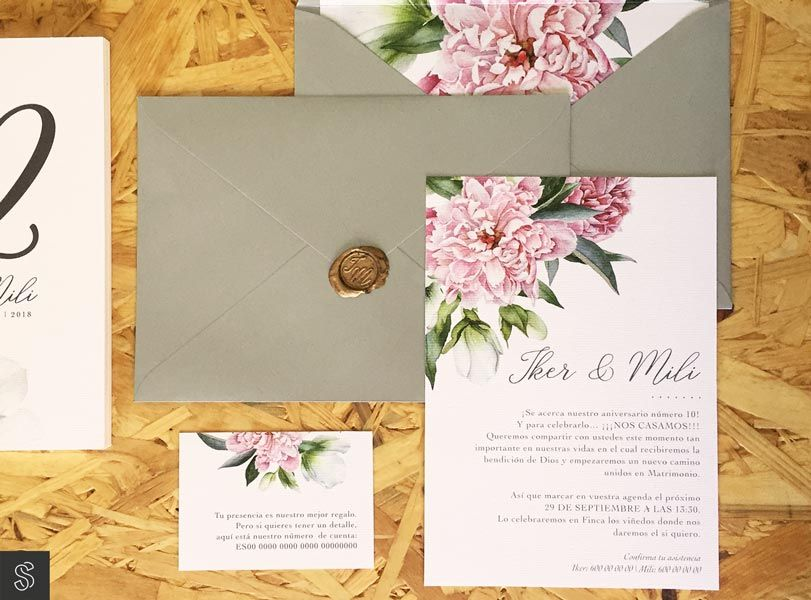 invitaciones con sobre plateado y forro decorativo cerrado con sello de lacre personalizado con las iniciales de los novios. La invitación y la tarjeta del número de cuenta también son en papel verjurado. El conjunto está decorado con motivos florales.