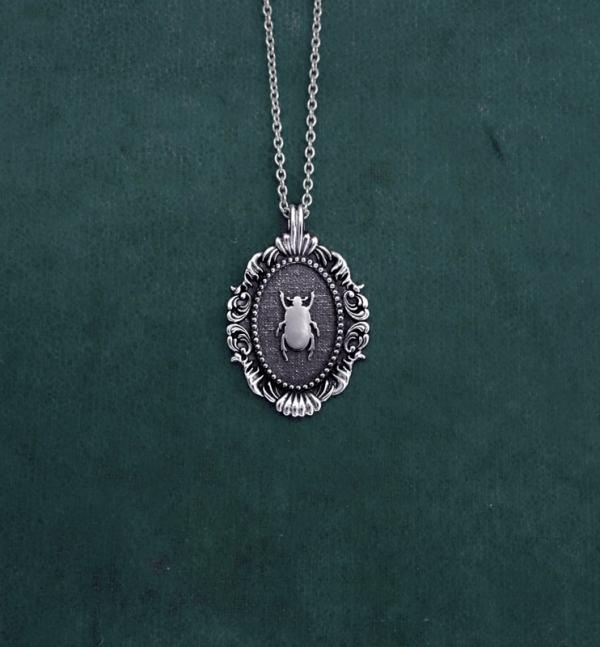 Petit collier scarabée noir egyptien dans cadre ovale baroque inspiré des cabinets de curiosités de fabrication artisanale | Res Mirum