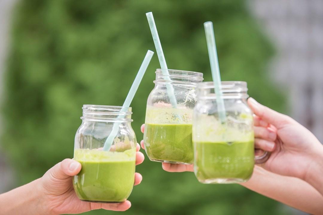 Three glasses of juice held up
