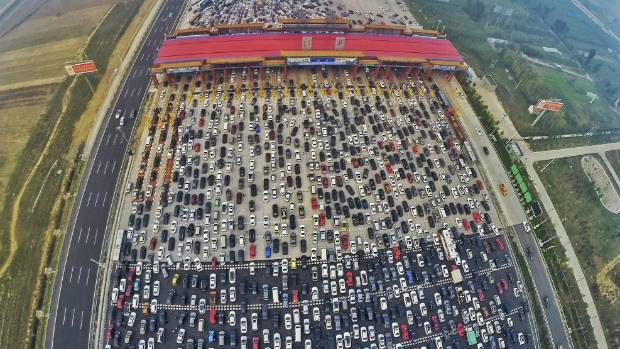 Vehicles are seen stuck in a traffic jam near a toll station as people return home at the end of a week-long national ...