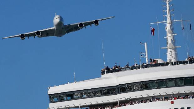 An Airbus A380 flies over the Queen Mary 2 ocean liner.