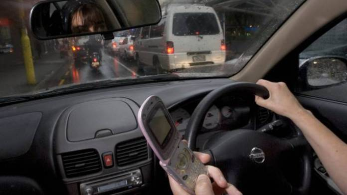 It's against the law to use a handheld device, even an old-school flip phone, while driving, and that includes while stationary at intersections or in heavy traffic.