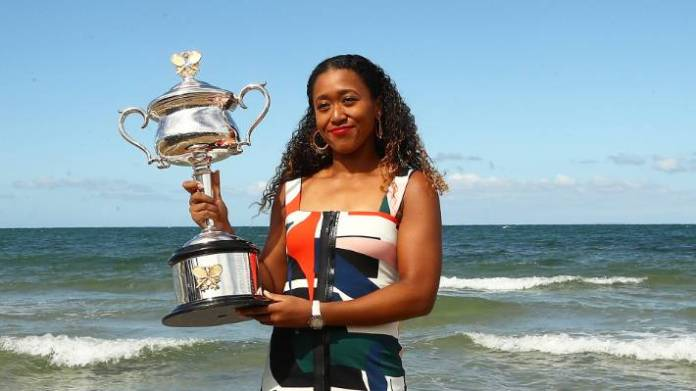Naomi Osaka shows off the Daphne Akhurst Memorial Cup at Melbourne's Brighton Beach, the day after her Australian Open triumph.