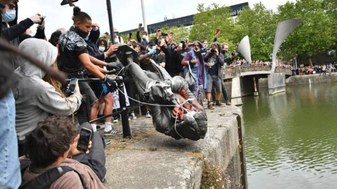 Protesters throw a statue of slave trader Edward Colston into Bristol harbour, during a Black Lives Matter protest rally.