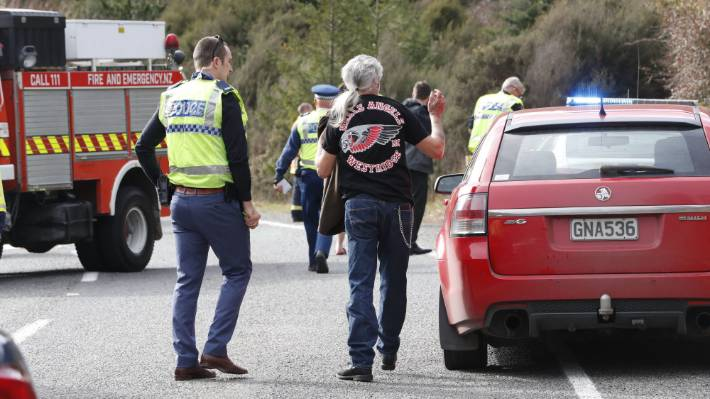 A police officer speaks to a Hells Angel member at fatal crash involving a motorcyclist and truck on State Highway 6.